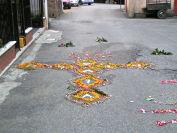 Croce di fiori sull'asfalto